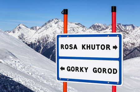 Sochi, Russia - January 20, 2013: Information navigation direction sign on metal plate bifurcating streams to Rosa Khutor and Gorky Gorod ski and snowboard resorts with mountain peak. United ski pass Éditoriale