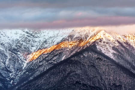Beautiful scenic winter sunset mountain landscape of Main Caucasus ridge with snowy mountain peaks covered with clouds, Sochi, Russia. Stock Photo