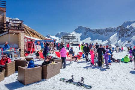 Sotschi, Russland - 25. März 2014: Wintersport- und Unterhaltungsaktivität für Skifahrer und Snowboarder. Leute chillen Apres Ski unter freiem Himmel unter blauem Himmel im Skigebiet Gorky Gorod