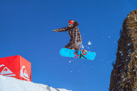 Sochi, Russia - March 25, 2014: Man snowboarder flies in the air from a jump on blue sky and mountain rock background at winter Redakční