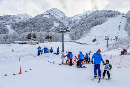 Sochi, Russia - January 9, 2015: Junior ski downhill competition is held annually on snowy slopes of Gorky Gorod winter mountain ski resort. Children skiers queue up to start riding the ski track