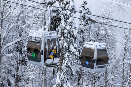 Sochi, Russia - January 9, 2015: Cable way ski lifts in Gorky Gorod winter mountain ski resort can transport ski and snowboard riders until June. Two cabins on snowy background scenic close up view Editorial