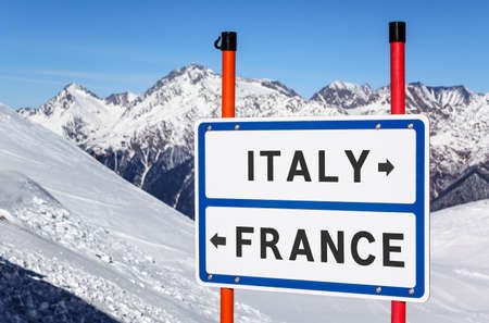 Italy or France choice to ski or snowboard. Information sign with direction arrows on winter mountain peaks under blue sky background. Banque d'images