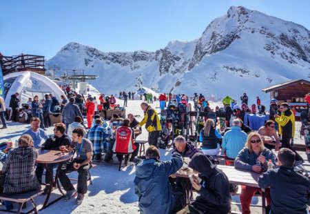 Sotschi, Russland - 13. Februar 2014: Verschneite Skipisten von Gorky Gorod Mountain Ski Resort. Leute, die Mahlzeiten im Freien im Après-Ski-Café gegen den schneebedeckten Aibga-Berggipfel essen