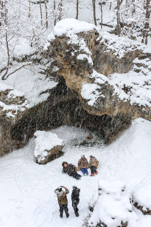 Maikop, Russia - January 3, 2009: Group of plump aged women are wallowing in the snow and taking photo on the frozen Belaya rivers bed during hard winter snowfall