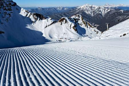 Sochi, Russia - January 20, 2013: Snowcat prepared Aibga snowy mountain cirque ski slope in Krasnaya Polyana resort, Sochi, Russia. Caucasus Mountains.
