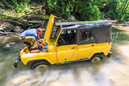 Sochi, Russia - June 9, 2009: Yellow off-road Russian car stuck in mountain river at sudden breakdown while jeeping. Driver fixing the auto with hood lifted up. Scenic view in sunny summer forest Editorial