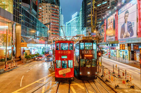 Hong Kong, China - 18 de enero de 2016: El transporte de tranvía es popular en Hong Kong. La red de tranvías proporciona transporte de personas a lo largo de la isla de Hong Kong. Paisaje nocturno con alumbrado público.