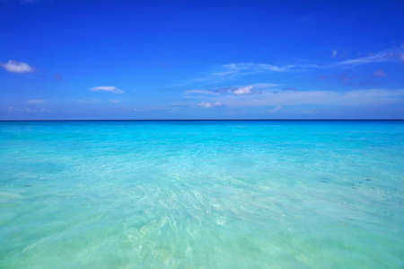 Scenic seascape of azure transparent ocean water and blue sky. Tropical beach with white sand. Idyllic scenery of seaside resort. Exotic travel destination for holiday and vacation. Stock fotó