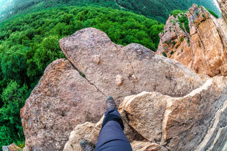 Man hiker steps on the edge of mountain rock above precipice with green forest trees underneath. Caucasus mountain summer scenery. Eagles Rock Shelf on Lenina Mount. Fisheye view