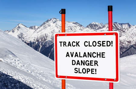 No skiing track closed avalanche danger slope. Security interdiction sign with black text on white background in red frame against snowy winter mountain peak and blue sky. Reklamní fotografie