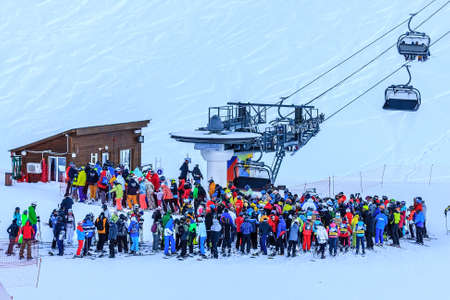 Sochi, Russia - January 7, 2018: Crowds of skiers and snowboarders queue by chair ski lift station of Gorky Gorod mountain ski resort on winter day Editorial