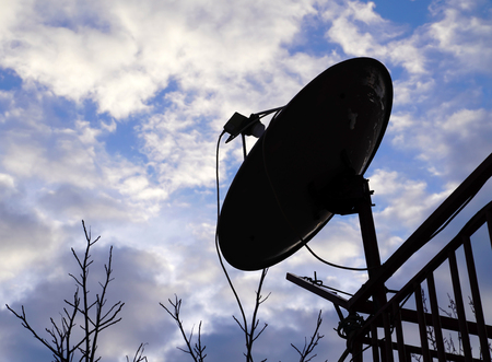 Silhouette of home satellite dish antenna on the balcony with cloudy blue sky Stock Photo