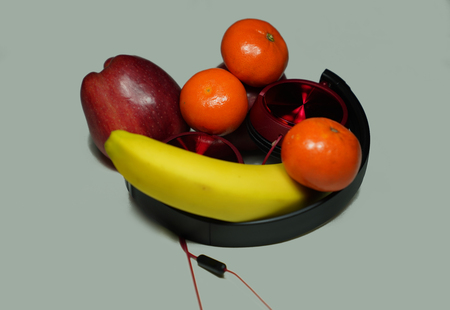 Red apples, mandarins and banana with red headphones on white-background (Music is food for the soul