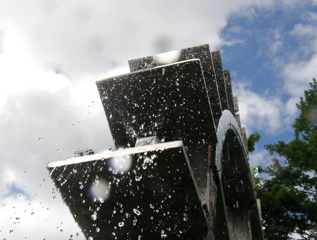 Water mill bottom up view against sky, water dropping from water mill to the camera Stock Photo