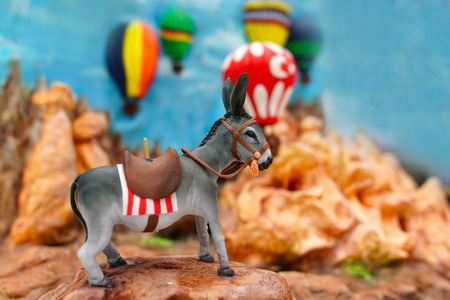 A part of figurine describing Cappadocia with donkey, fairy chutes and hot air balloons all together Stock Photo