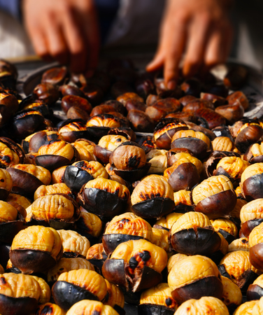Man grilling chestnuts for sale on street Stock Photo - 100257367