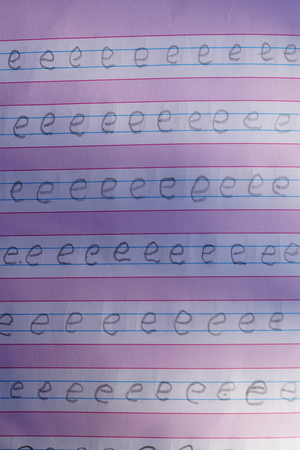 Childs hand writes in a notebook with a pencil
