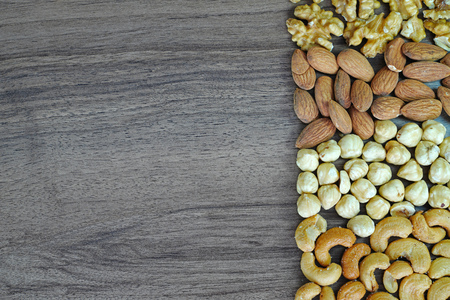 Nuts background, walnut, almond, hazelnut and cashew nuts in order on wooden table 版權商用圖片