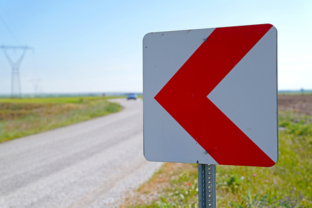 Road signs warning drivers about ahead dangerous curve and blurred car in background