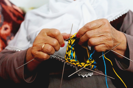 Close up of old woman hands knitting colorful wool sock with knitting needles Stok Fotoğraf