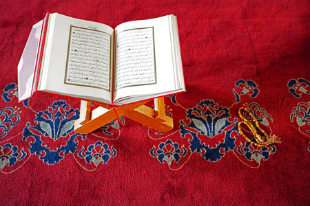 AnkaraTurkey- June 2 2018: Holy Koran on stand and prayer beads on red carpet in Kocatepe Mosque