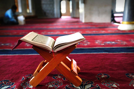 Holy Koran on stand on red carpet and blurred interior of a mosque in background
