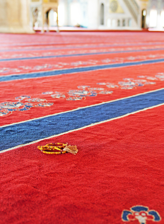 Muslim prayer beads on red carpet in a mosque