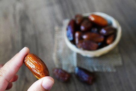 Human finger holding single date fruit and blurred dates filled bowl in background