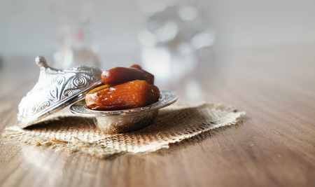Fresh fruit dates in a silver metal bowl on a piece of sackcloth on walnut wooden table