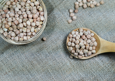Dry chickpeas in a basket bowl and wooden spoon on sacking