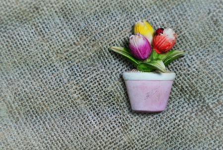 Tulips flower in vase as magnetic souvenir on sackcloth