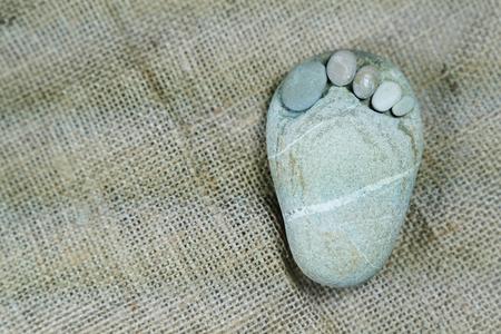Tiny stone feet on sackcloth background