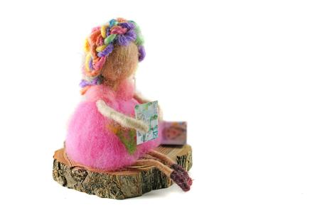 Felt doll sitting on wood and reading on isolated white background