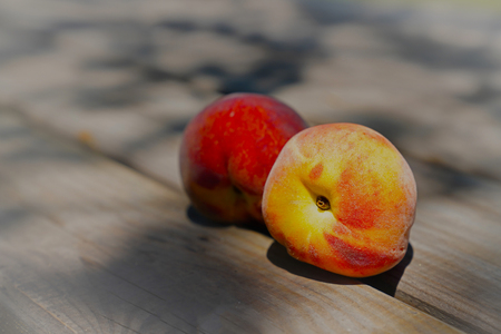 Two ripe peaches on wooden table