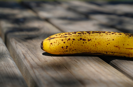Delicious ripe yellow banana fruit on rustic wooden table