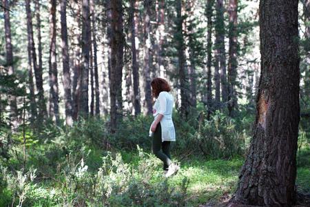 Woman walking on grass in a pine forest under sun light which reaches ground Stok Fotoğraf
