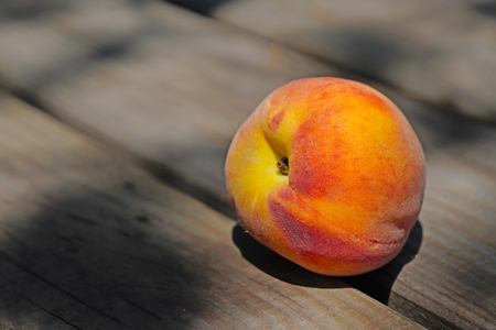 One ripe peach on wooden table