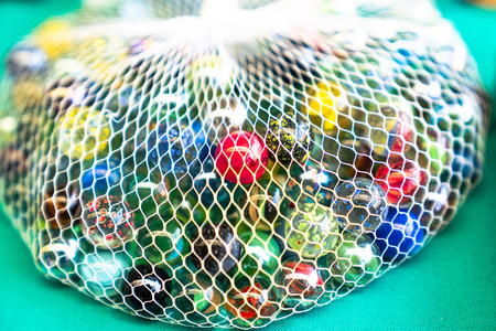 Colorful glass marbles in net Stok Fotoğraf