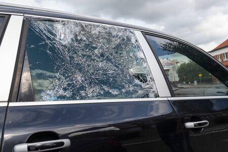 Closeup picture of black stolen damage car broken glass windows