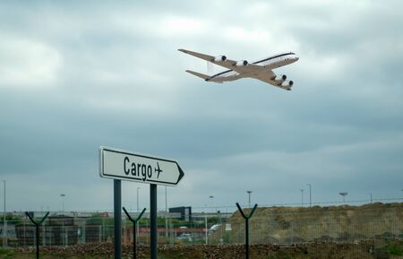 Air cargo sign on ground and a cargo flight on the air