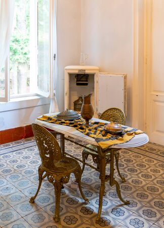 Antique marble dining table and antique metal chair and refrigerator in a classic and modern kitchen