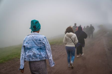 Back view of refugees walk to the border in a cold day under fog