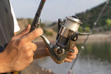 Male hand holding fishing rod and reeling the other hand.