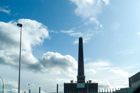 Old factory chimney on blue sky background
