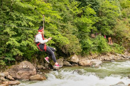 Rear view of tourist girl gliding on the zip line trip on Firtina valley, Rize, Turkey