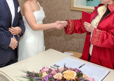 Marriage registrar congratulates new couple and gives the family registry to the bride.