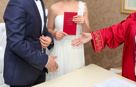 Ankara/Turkey- December 12 2014: Marriage registrar congratulates new couple and gives the family registry to the bride.