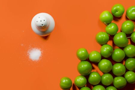 Pile of green plum fruit with salt isolated on orange color background