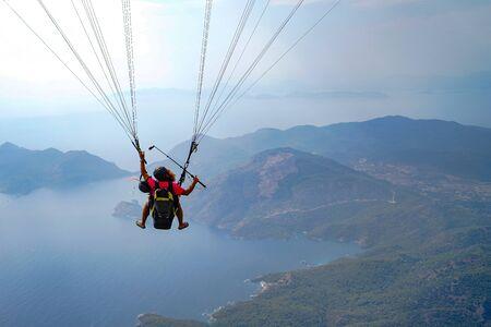 Fethiye, Mugla/Turkey- August 19 2018: Tandem paragliders on Mediterranean